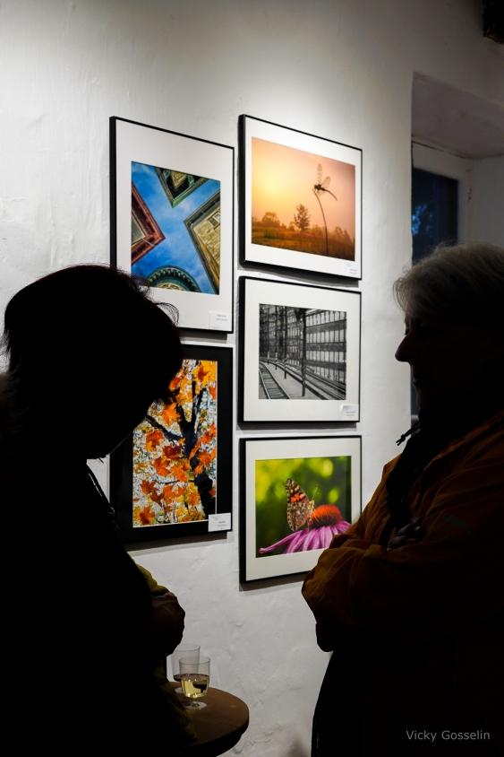 Des visiteurs admirent le montage des photos originales qui paraissent sur l'affiche